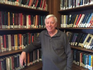 Professor John Kincaid stands in front of a full bookshelf.