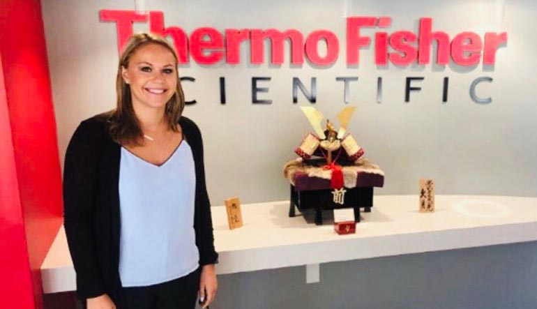 Lauren Johnson '19 stands in front of the Thermo Fisher logo where she was hired.