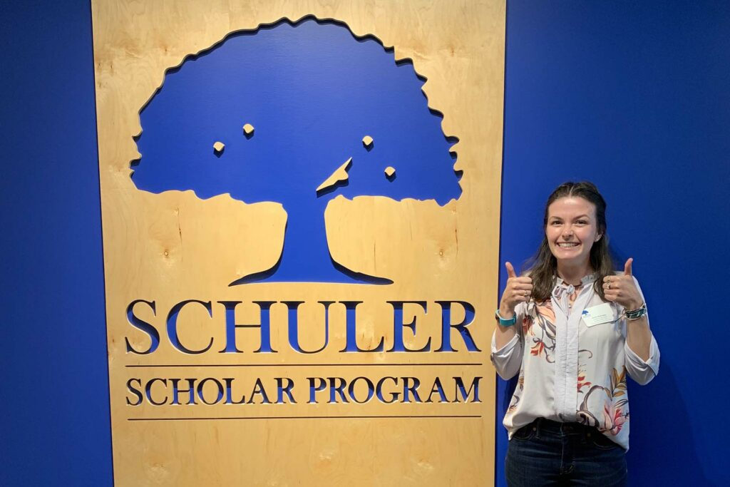 Molly Martindale '19 stands in front of the blue tree logo of her new employer.