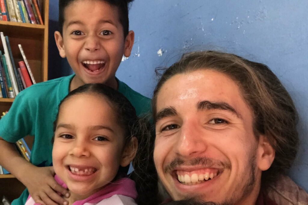 Remy Oktay '23 poses in a selfie with some children who smile big