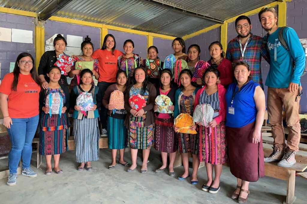 Remy Oktay '23 poses with a group of women who help make menstruation products