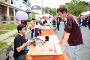 a student looks at dan goodman's exquisite handmade rings at block party