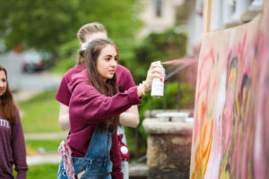 students legally apply graffiti to a sign at block party