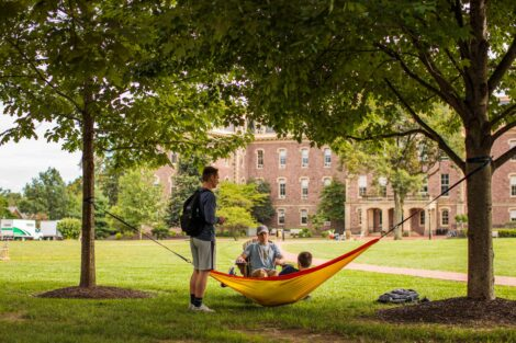 students talk in a hammock in front of pardee