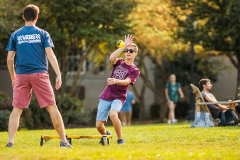 a student plays spike ball on the quad