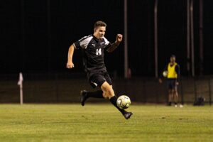 A Lafayette soccer player dribbles with the ball.