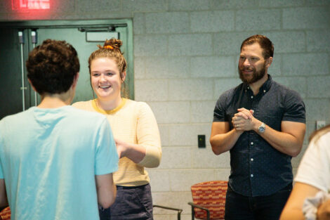 A member of Improvised Shakespeare Company watches two students do an improvisation exercise.