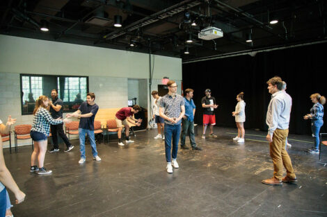Students stand and do acting exercises during a workshop held by Improvised Shakespeare Company.