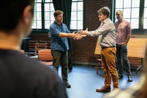 Two members of Improvised Shakespeare Company prepare to grasp hands together during a workshop