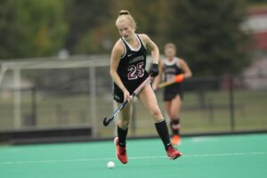 Anna Steps '21 advances the ball in a field hockey game against Temple.