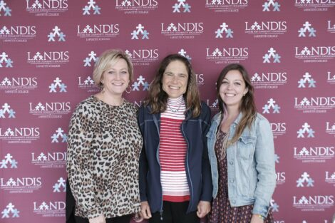 Landis staff members stand before Landis backdrop