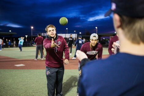 Baseball players throw balls to miracle league players