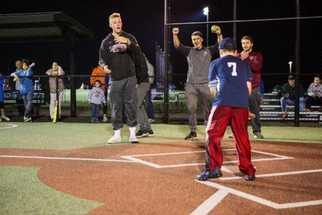 Baseball players cheer as batter hits