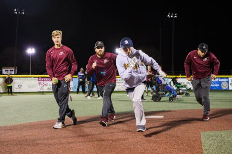 Baseball players run in stride with player as he rounds the base