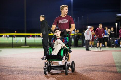 Lafayette player pushes boy in wheelchair