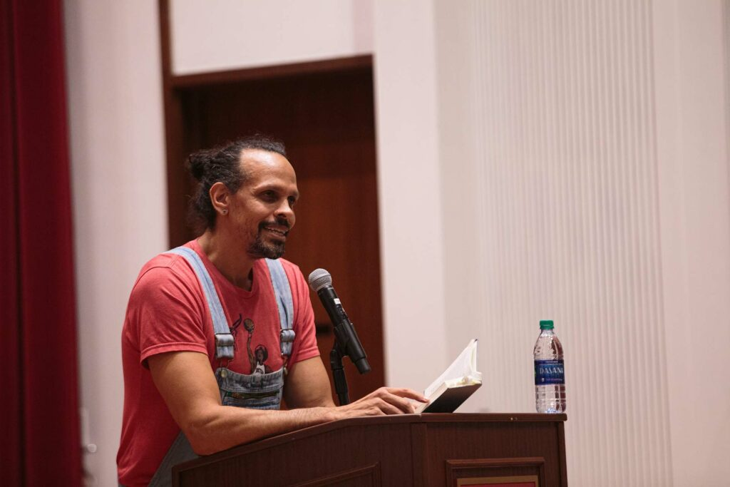 Ross Gay '96 stands at a lectern and speaks with a crowd at Colton Chapel
