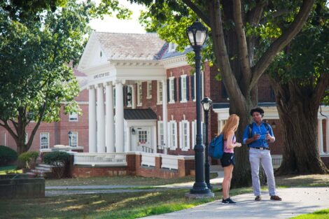 students talk in front of ramer history house