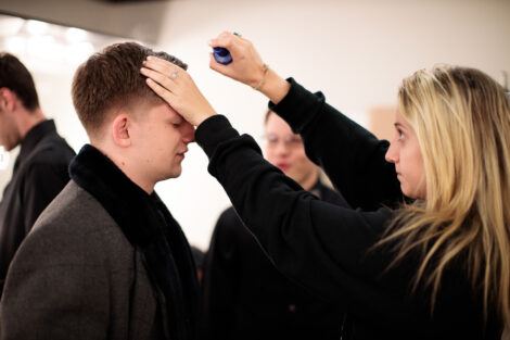 students prepare hair and makeup backstage