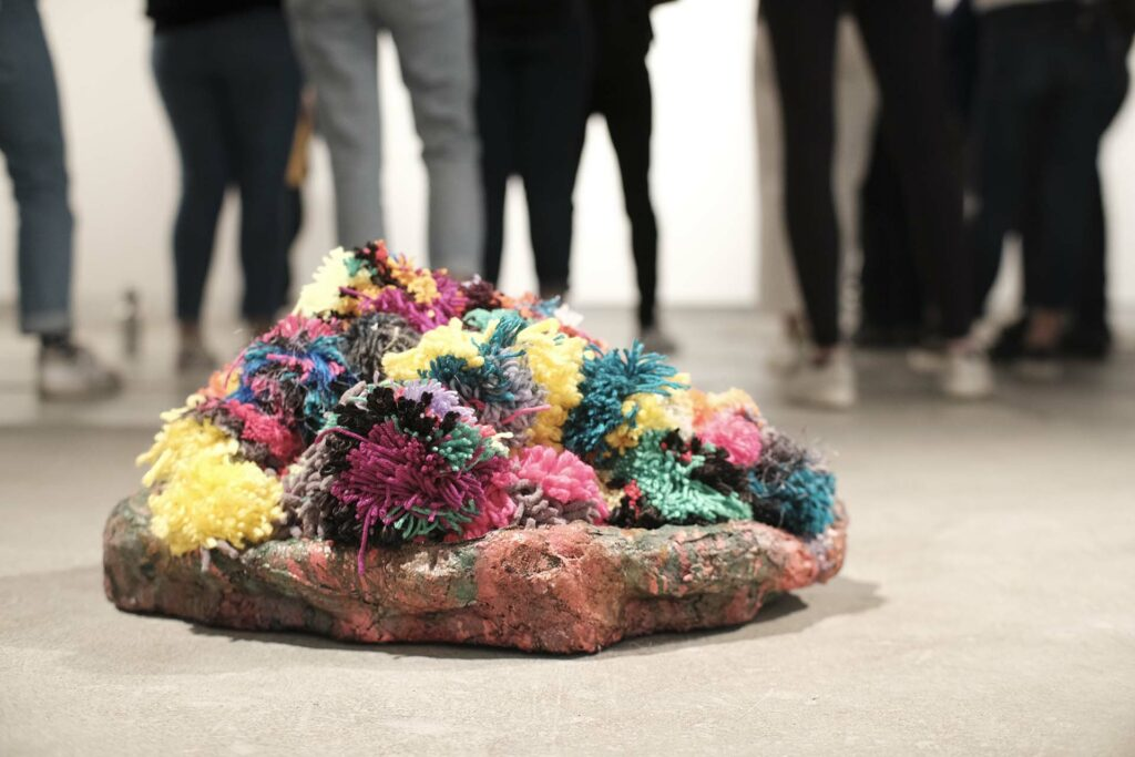 A pile of pom poms fills a sculptural dish