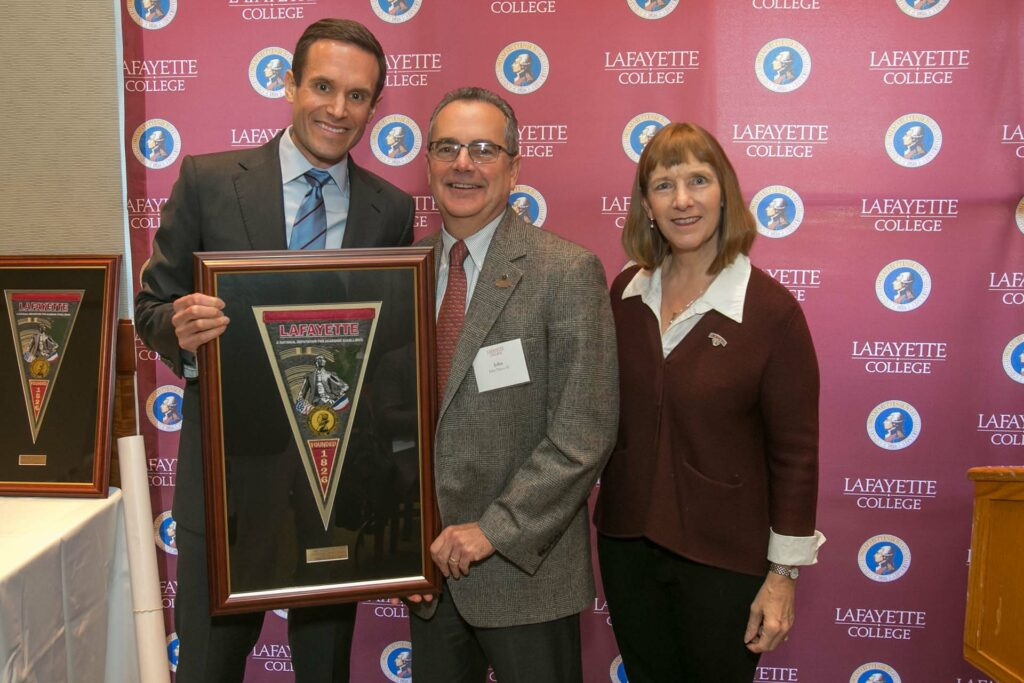 John holds a framed award and is flanked by the alumni and college presidents