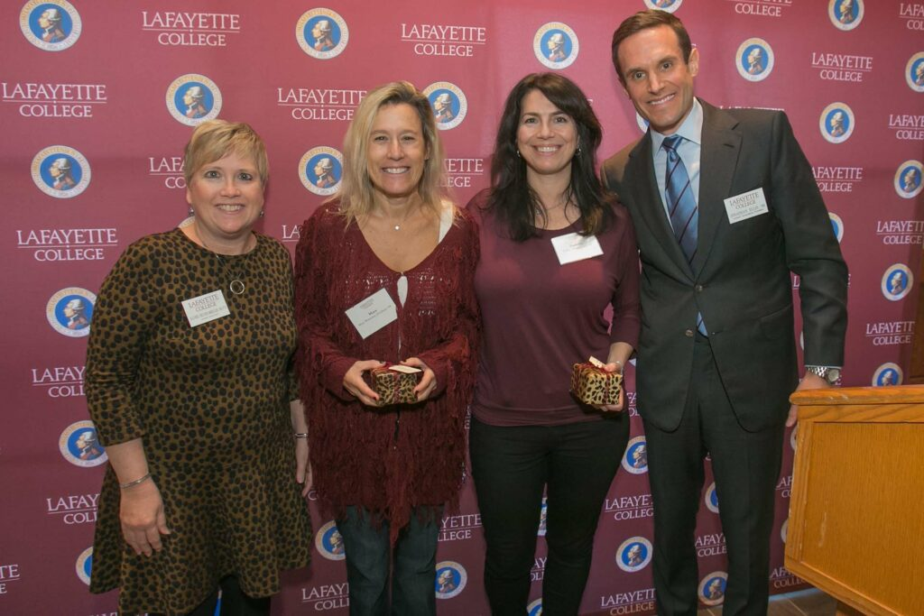 Mara and Kathryn hold awards flanked by alumni relations director and president