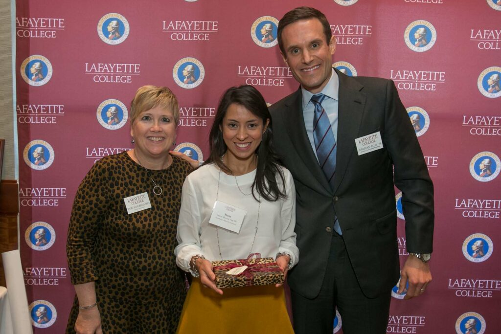 Maria holds her award flanked by the alumni relations director and president