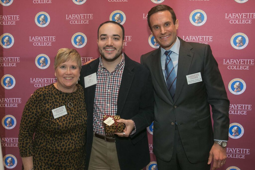 Matt holds an award and is flanked by the alumni relations director and president