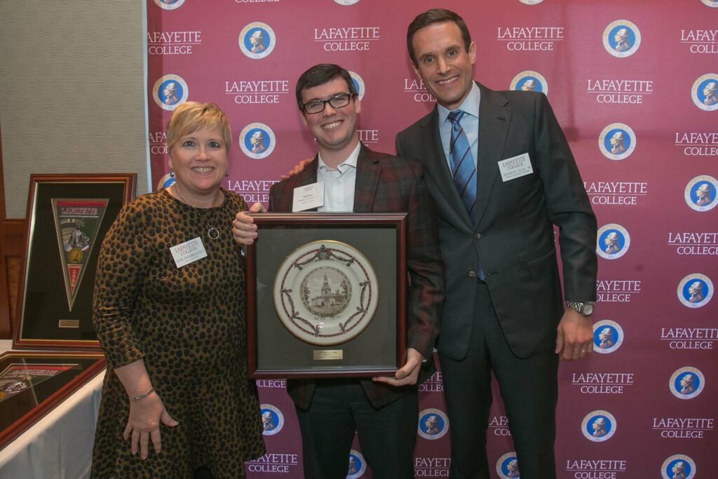 Matt holds framed award and is flanked by alumni relations director and president