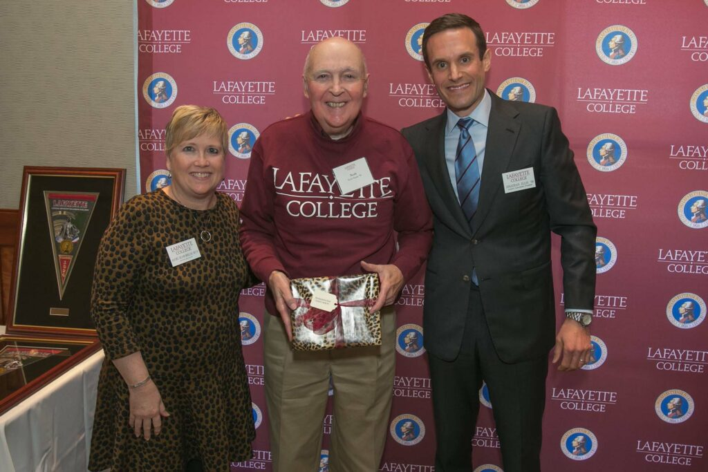 Norb holds an award flanked by the alumni relations director and president