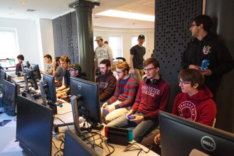 A group of students from Lafayette and Lehigh Esports clubs sit together and play video games.