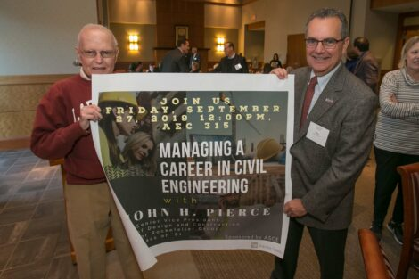 John Pierce holds a poster on one side while Professor Dave Veshoski
