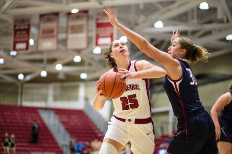 Natalie Kucowski gets ready to shoot the ball while being defended in a women's basketball game.