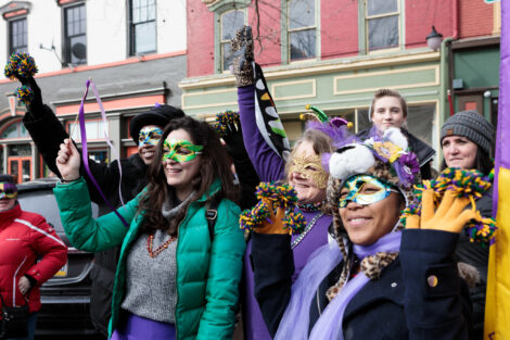 students in mardi gras apparel wave tiny pom poms or leopard gloves in downtown easton