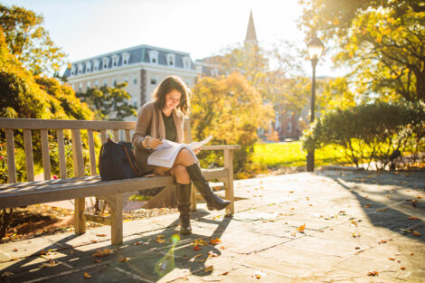 student sitting on a bench with beautiful fall leaves and a lens flare in the bottom left corner with south college in the background