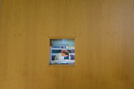 a student takes a final seen through a door