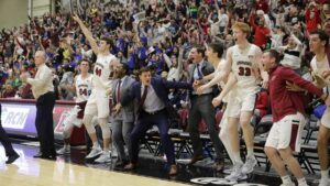 Men's basketball players and fans celebrate the game-winning basket against Colgate.