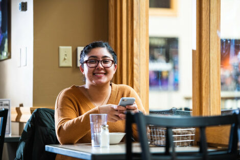 A student sitting at a table smiles for the camera on the first day of spring semester.