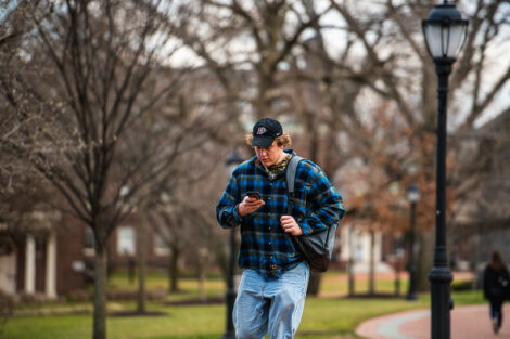 A student looks at his phone while walking on campus on the first day of spring semester.