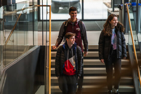Three students walk down steps in Rockwell Integrated Sciences Center on the first day of spring semester.