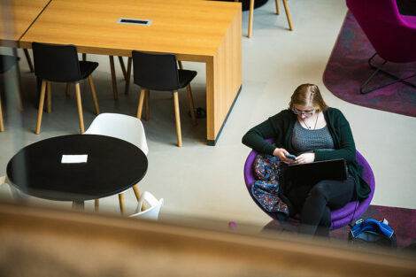 A student uses her smartphone while sitting in Rockwell Integrated Sciences Center on the first day of spring semester.