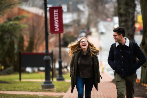 A student laughs while talking with a friend and walking on High Street on campus on the first day of spring semester.