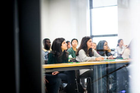Students listen to their professor in a classroom on the first day of spring semester.