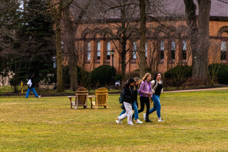 Four students walk together on the Quad near Van Wickle Hall on the first day of spring semester.