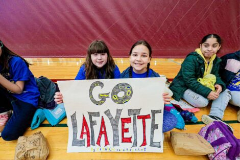 Elementary students are ready to cheer with a homemade sign.