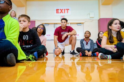 Athlete helps students listen to lesson