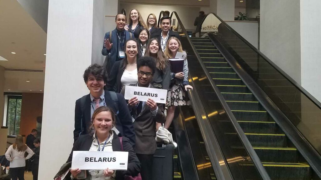 Model UN students hold signs representing their country Belarus