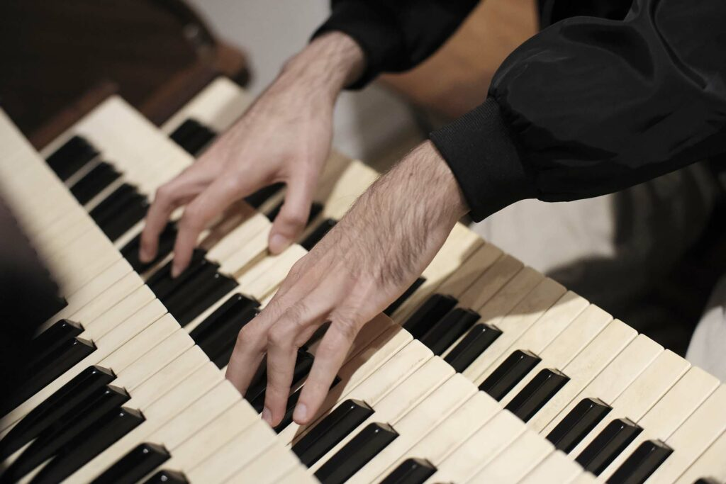 Sean Gough's hands on the keyboard of the organ in Colton Chapel