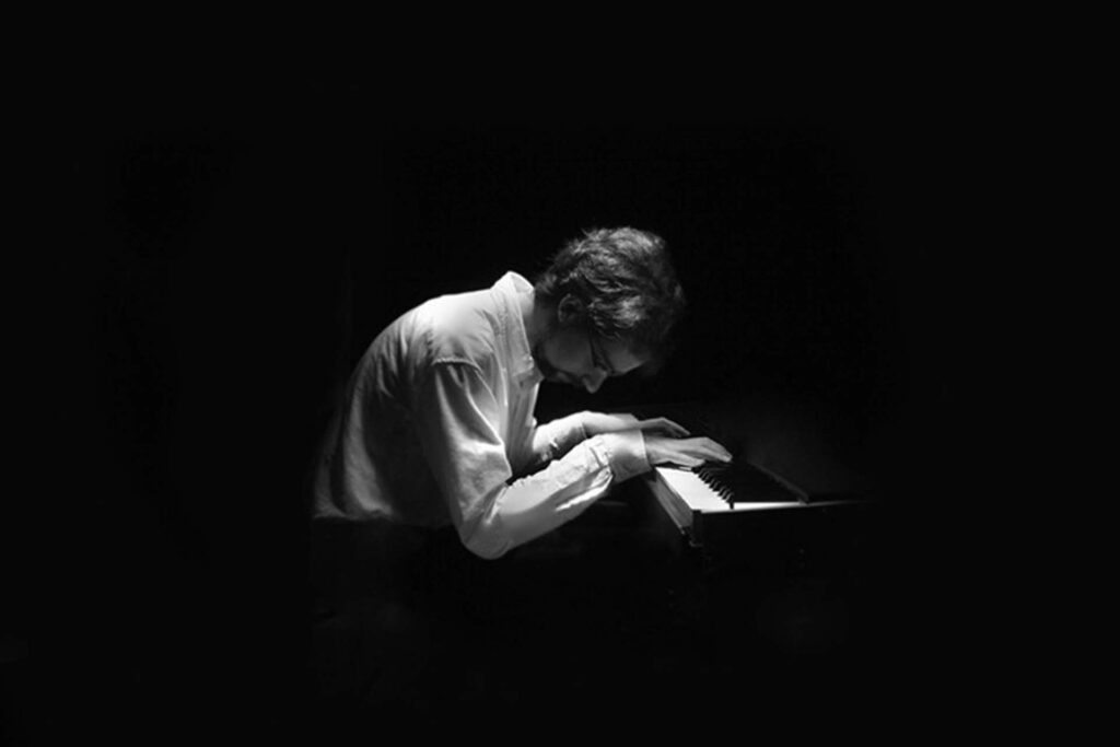 Sean Gough '09 leaning over piano keyboard in stark black and white