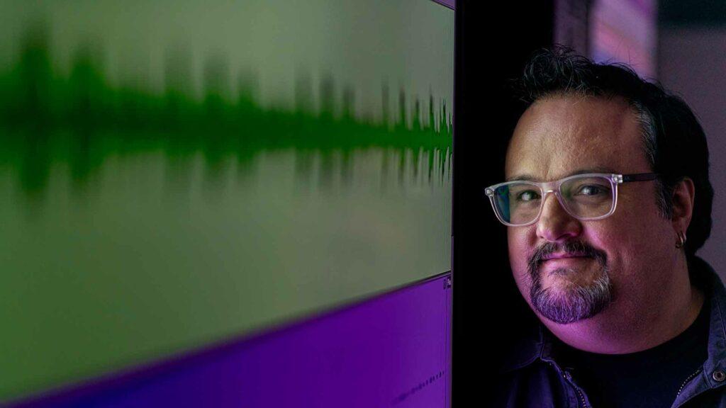Chris Badami stands next to sound waves
