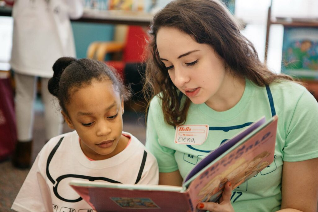 Landis Center student volunteer reads to an area elementary student